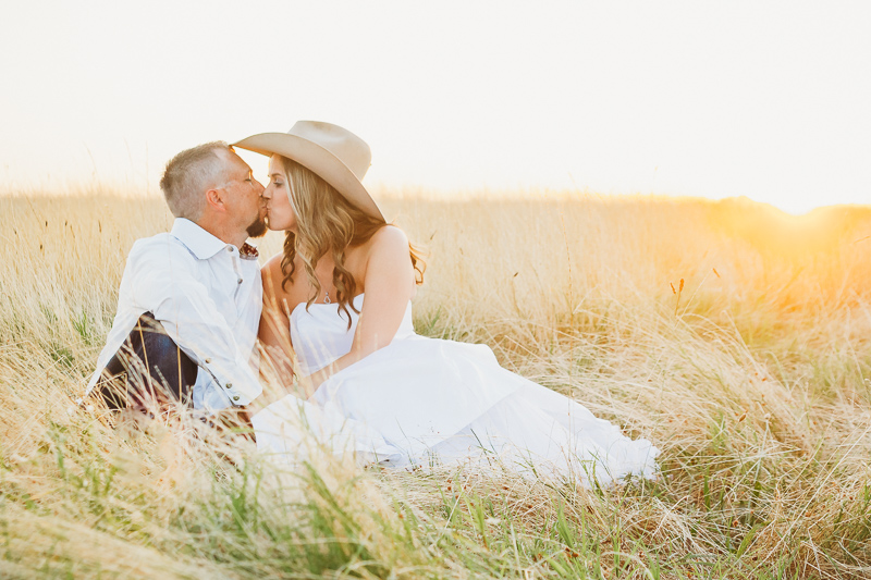 Wedding couple sitting in tall grass at sunset. Bride is wearing a cowboy hat.